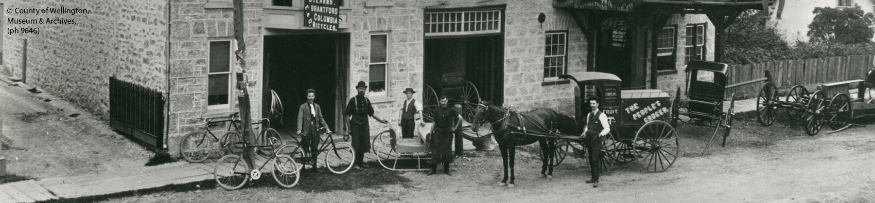 Men, horses and wagons standing in front of building
