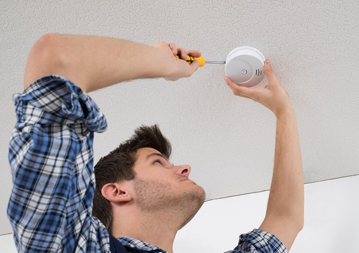 man changing a smoke detector